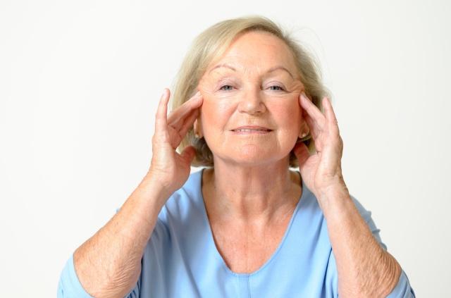 Seniorin zieht an ihrer Haut im Gesicht